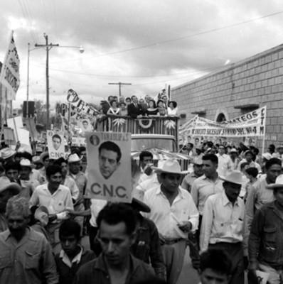 Adolfo López Mateos con mujeres a bordo de un camión saludando partidarios