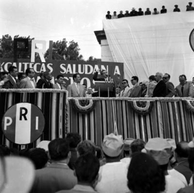 Adolfo López Mateos pronunciando un discurso en un presídium durante su campaña electoral por Tlaxcala, toma en contrapicada