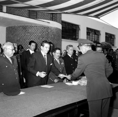 Adolfo López Mateos entregando documento a miembro del colegio militar durante la inauguración de sus cursos