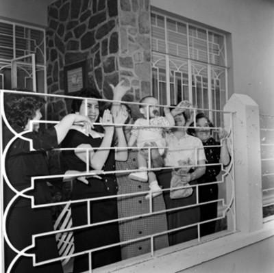 Mujeres ovacionando a Adolfo López Mateos desde el patio de una casa
