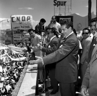 Adolfo López Mateos escuchando las palabras de un orador y saludando a la población en un mitin