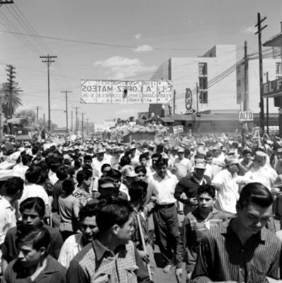 Adolfo López Mateos y comitiva en un automóvil saludando, durante su recorrido a una multitud