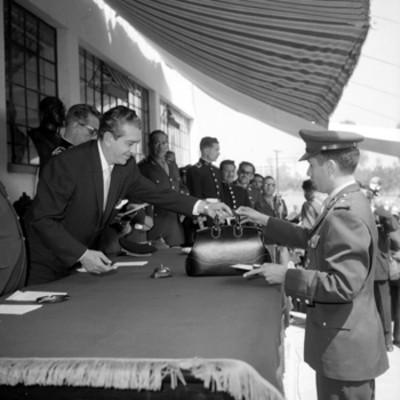 Adolfo López Mateos obsequiando un libro a un estudiante, de la Escuela Médico Militar