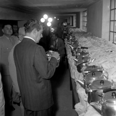 Adolfo López Mateos observando una olla elaborada en la fábrica de Industria Militar