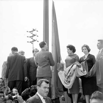 Antonio Ortiz Mena izando la bandera Nacional, señalando así, la mexicanización de la industría eléctrica