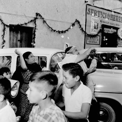 Mujeres en la calle arrojando confeti durante la gira electoral de Adolfo López Mateos en Actopan