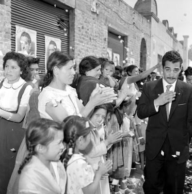 Adolfo López Mateos recorriendo una calle tomado del brazo con mujeres durante un mitin de apoyo a su campaña por Mixquiahuala y Tlahuelilpan