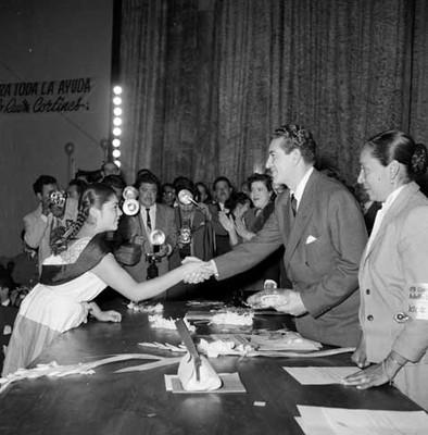 Adolfo López Mateos saludando a la campesina Estela Oropeza en el Cine Reforma