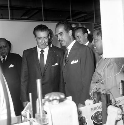 Adolfo López Mateos y empresario observando la maquinaria de una planta industrial