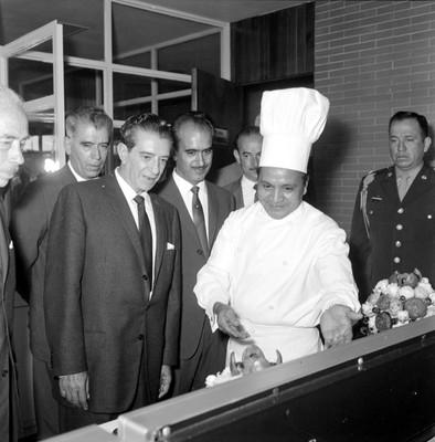 Adolfo López Mateos observando un platillo que le muestra un cocinero, en una conina de una planta industrial