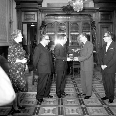 Adolfo López Mateos recibiendo el acta de Independencia del imperio mexicano departe de un individuo, en presencia de Gustavo Díaz Ordaz