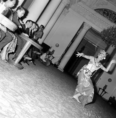 Bailarina indonesa durante evolución de danza folclórica en un salón