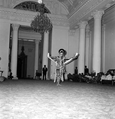 Bailarina indonésica durante evolución de danza folclórica en un salón
