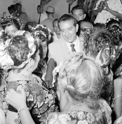 Adolfo López Mateos rodeado por mujeres vestidas con trajes regionales, durante su campaña electoral por Juchitán