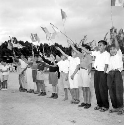 Niños portando banderas saludan a Adolfo López Mateos a su paso para Valladolid