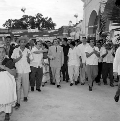 Adolfo López Mateos camina en compañía de funcionarios por una calle de Hoctún en su gira electoral