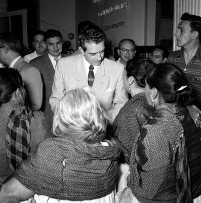 Adolfo López Mateos conversa con mujeres indígenas en el interior de un edificio
