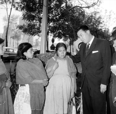 Humberto Romero conversando con viudas en una calle, durante le entrega de la indemnizacvión de mineros fallecidos en la mina de el Olivar del Conde