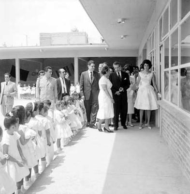 Adolfo López Mateos conversando con una mujer durante la inauguración de una escuela