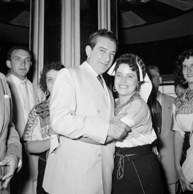 Adolfo López Mateos abrazando a una mujer con traje regional durante un banquete a su campaña en el Hotel Bonampak en Tuxtla Gutiérrez