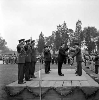 Adolfo López Mateos recive una bandera en una ceremonia Militar