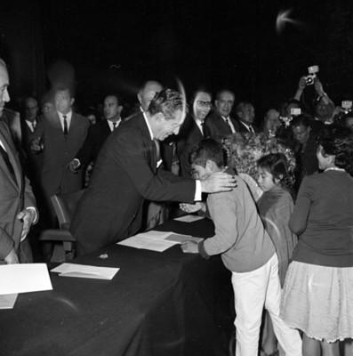 Adolfo López Mateos es saludado por un niño, en la entrega de títulos de propiedad