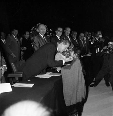 Adolfo López Mateos es saludado por una niña, durante la entrega de títulos de propiedad