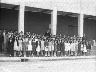 Maestros y alumnos en el patio de una escuela, retrato de grupo