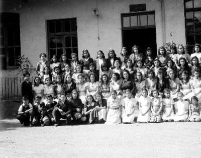 Maestra y alumnos en el patio de una escuela, retrato de grupo