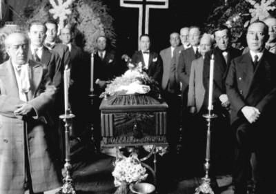 Pastor y demás personas montando guardia a un féretro, en una agencia funeraria