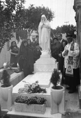 Sacerdote y otras personas ofreciendo un homenaje luctuoso en la tumba de Javier Enciso