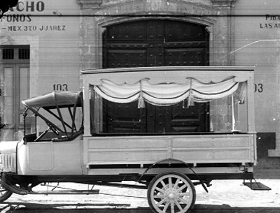Carroza funebre fuera de una empresa funeraría