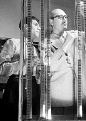 Carlos Velo y otro hombre observan películas cinematográficas