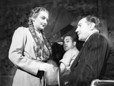 Actriz maquillada por mujer durante la filmación de una película en un estudio cinematográfico