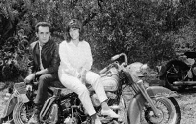 Ismael Casasola acompañado por una mujer en una motocicleta, durante el descanso de una filmación cinematográfica