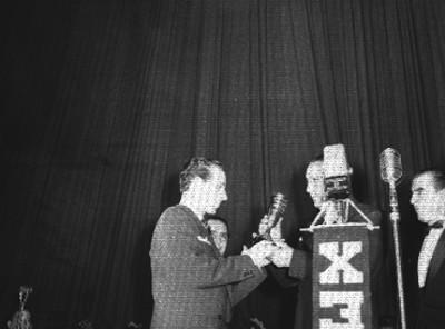 Productor de cine recibiendo el premio CineMex, de manos de un actor
