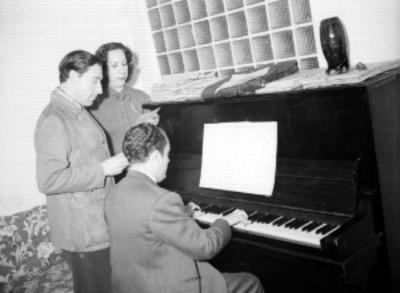 Díaz Conde, Antonio Garaza y C. Guerrero de Luna durante la interpretación de una melodia, en la sala de una casa