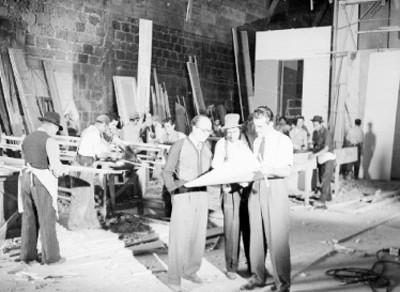 Dibujantes y carpinteros trabajando en la construcción de un foro
