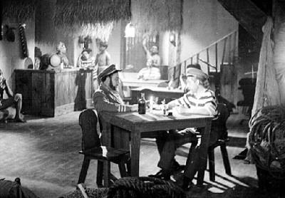 Marino observando una botella en una cantina, escena de película