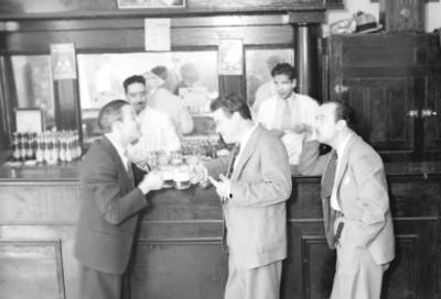 Actores brindando en la barra de una cantina, escena de teatro historieta