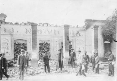 Soldados y civiles junto a ruinas de un edificio
