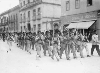Soldados huertistas desfilan por una calle