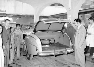 Jorge Negrete abriendo la cajuela de un automóvil en una gasolinera