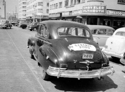 Automóvil en la avenida Juárez con propaganda de la General Popo