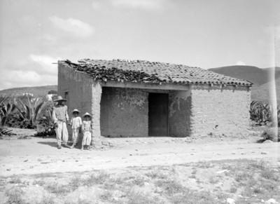Hombre y niños junto a una casa de adobe