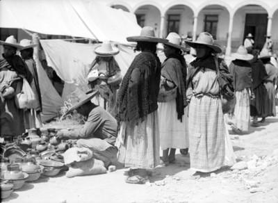 Mujeres y vendedor de cerámica en un tianguis