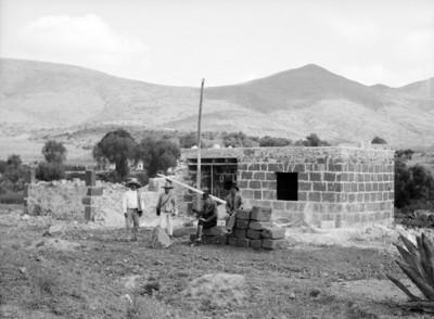 Otomíes frente a una casa rústica en construcción, retrato de grupo