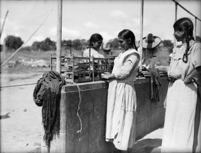 Mujeres otomíes junto a jaulas con aves en su interior