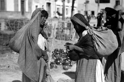 Mujeres con mecapal en un tianguis
