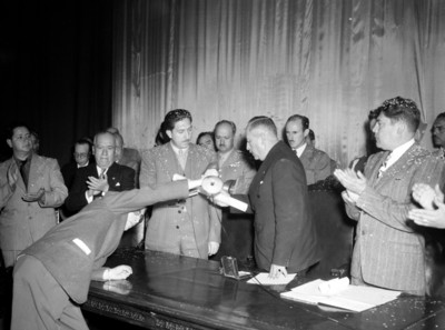 Miguel Alemán Valdés recibe reconocimiento de manos de un funcionario
